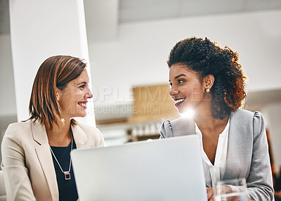 Buy stock photo Cropped shot of two businesswomen working together on a laptop in an office
