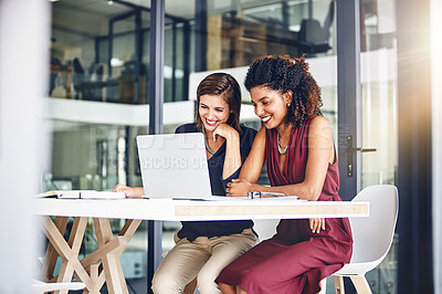 Buy stock photo Cropped shot of two young businesswomen using a laptop in an office