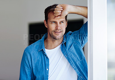 Buy stock photo Cropped shot of a handsome man looking pensive while leaning against a door