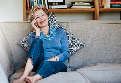 Buy stock photo Shot of a relaxed senior woman using a phone at home on the sofa