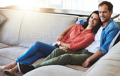 Buy stock photo Full length portrait of an affectionate couple sitting on the sofa at home