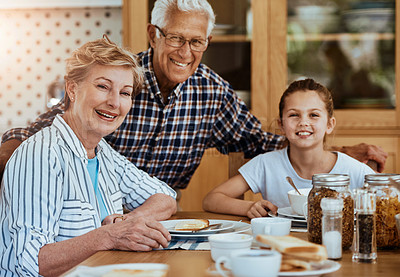 Buy stock photo Portrait of a little girl having breakfast with her grandparents at home