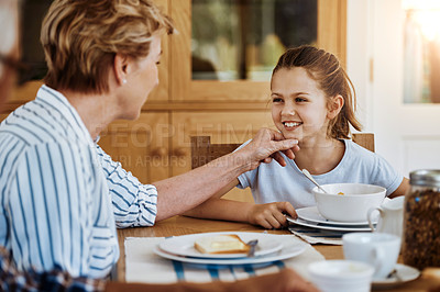 Buy stock photo Cropped shot of a little girl having breakfast with her grandmother at home