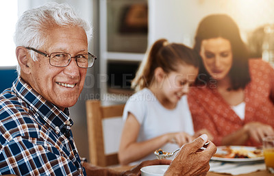 Buy stock photo Portrait of an elderly man enjoying breakfast with his family at home