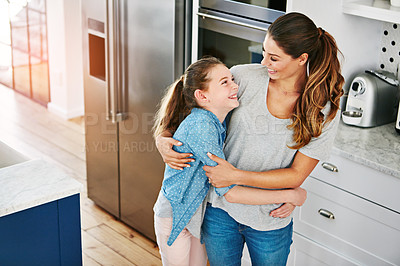 Buy stock photo Shot of a happy mother and daughter in a loving embrace at home