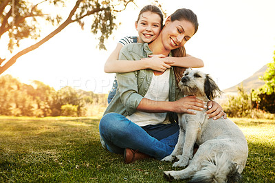 Buy stock photo Shot of a mother and her daughter playing with their dog at the park