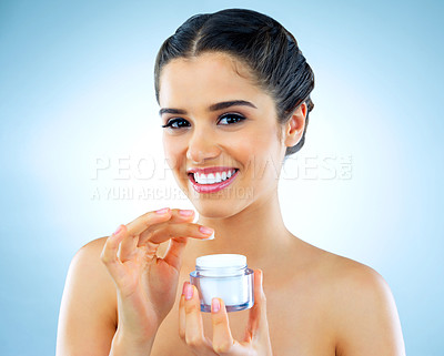 Buy stock photo Studio shot of a beautiful young woman applying moisturizer to her face against a blue background