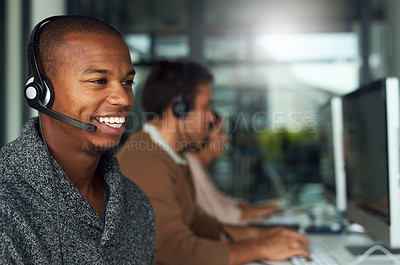 Buy stock photo Cropped shot of a call centre agent working in an office with his colleagues in the background