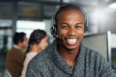 Buy stock photo Portrait of a call centre agent working in an office with his colleagues in the background