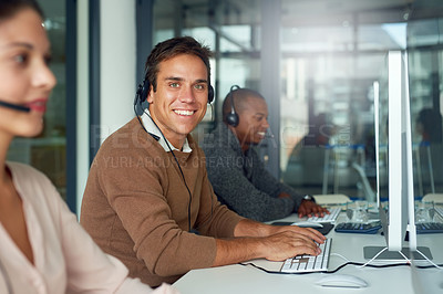 Buy stock photo Portrait of a call centre agent working alongside his colleagues in an office