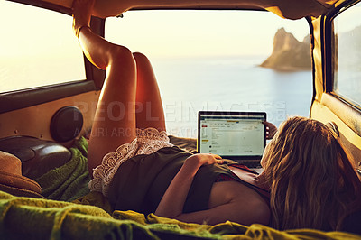Buy stock photo Shot of a young woman using her laptop while relaxing in the back of her car  on a roadtrip