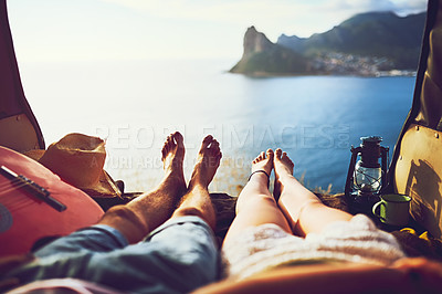 Buy stock photo Shot of an unidentifiable young couple relaxing inside their car during a roadtrip