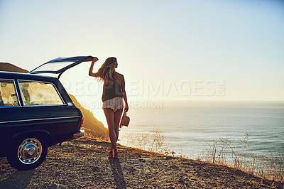 Buy stock photo Rearview shot of a young woman standing next to her car during a roadtrip