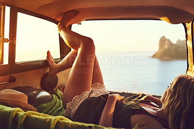 Buy stock photo Shot of a young woman relaxing in the back of her car  on a roadtrip