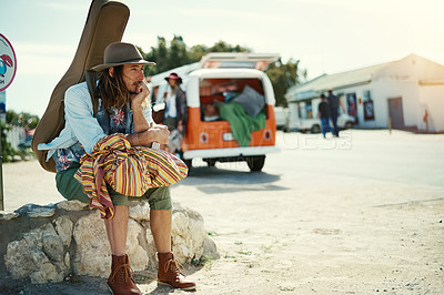 Buy stock photo Shot of a young man with a guitar on his back sitting at the side of the road with his girlfriend and van in the background