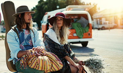 Buy stock photo Shot of a young hipster couple sitting at the side of the road with their broken down van in the background