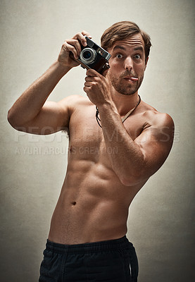 Buy stock photo Studio shot of a shirtless young man taking photos with a vintage camera while making funny faces