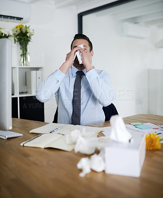 Buy stock photo Shot of a young businessman suffering with allergies at work