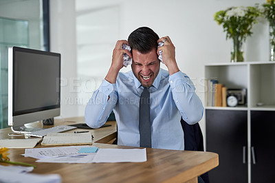 Buy stock photo Shot of a young businessman looking stressed out while working in an office