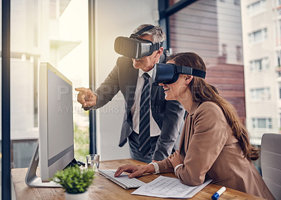 Buy stock photo Shot of two businesspeople wearing VR headsets while working on a computer in an office