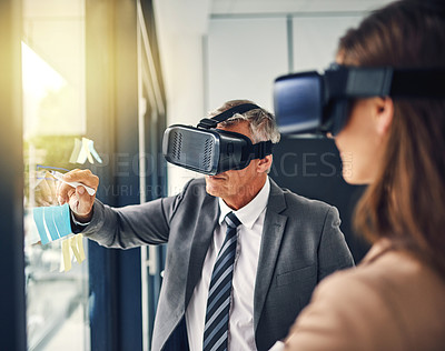 Buy stock photo Shot of two businesspeople wearing VR headsets while working with notes on a glass wall in an office