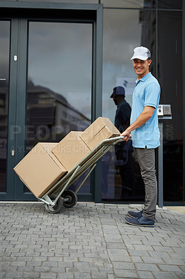 Buy stock photo Portrait of a courier pushing a trolley of boxes while making a delivery