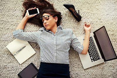 Buy stock photo High angle shot of a stressed out businesswoman sleeping on the floor in an office