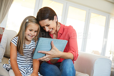 Buy stock photo Shot of a mother and her young daughter sitting together in the living room at home using a digital tablet