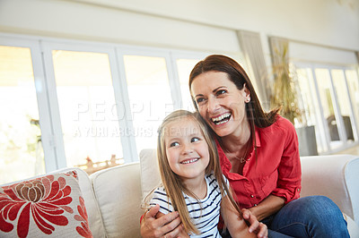 Buy stock photo Portrait of a mother and  her young daughter sitting together in the living room at home