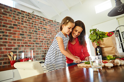 Buy stock photo Shot of a cute little girl chopping vegetables in the kitchen with her mother