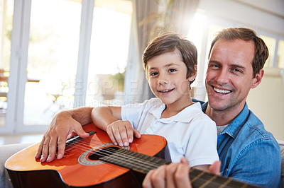Buy stock photo Shot of a father and his young son sitting together in the living room at home playing guitar