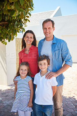 Buy stock photo Portrait of smiling parents and their young son and daughter standing outside in their yard on a sunny day