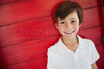 Buy stock photo Portrait of a smiling little boy standing against a red wall