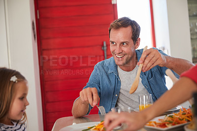 Buy stock photo Shot of a happy family enjoying a home-cooked meal together at the table