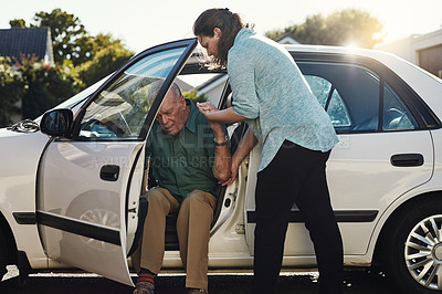 Buy stock photo Shot of a woman helping her senior father out the car