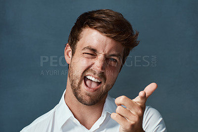 Buy stock photo Studio portrait of a handsome young man making a face against a dark background