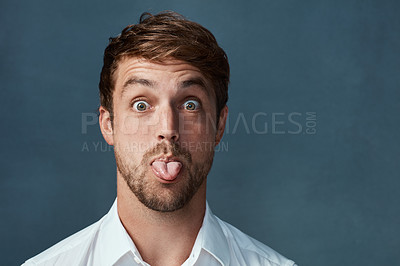Buy stock photo Studio portrait of a handsome young man sticking his tongue out against a dark background