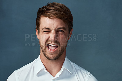 Buy stock photo Studio portrait of a handsome young man winking against a dark background