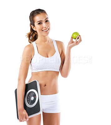 Buy stock photo Cropped shot of a young woman eating an apple while holding a scale