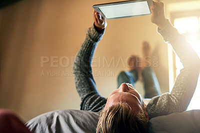 Buy stock photo Shot of a young man watching something on his digital tablet at home
