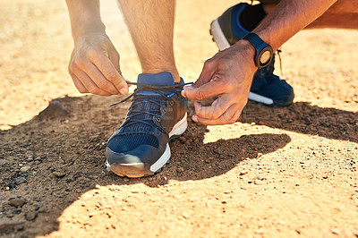 Buy stock photo Cropped shot of an unidentifiable man tying his shoelaces outside
