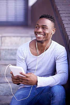 Buy stock photo Shot of a young man listening to music while sitting on a staircase outside