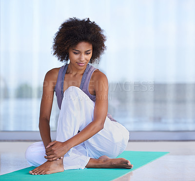 Buy stock photo Shot of an attractive young woman doing stretches on an exercise mat