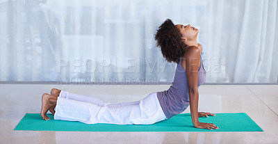 Buy stock photo Shot of an attractive young woman doing yoga on an exercise mat