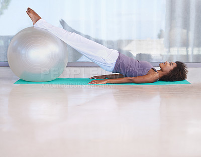 Buy stock photo Shot of an attractive young woman doing pilates with an exercise ball