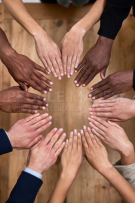 Buy stock photo High angle shot of a group of unidentifiable businesspeople making a circle with their hands in the office