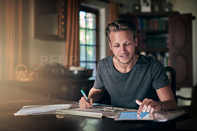 Buy stock photo Shot of a diligent young student using his tablet to do a homework assignment at home