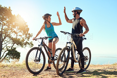 Buy stock photo Shot of a happy young couple out mountain biking together