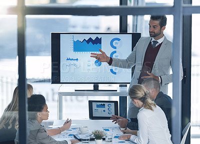 Buy stock photo Shot of a businessman discussing charts on a monitor to businesspeople in the boardroom