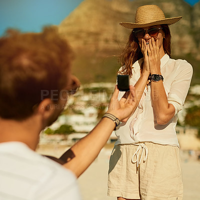 Buy stock photo Shot of a young woman getting engaged at the beach on a summer's day